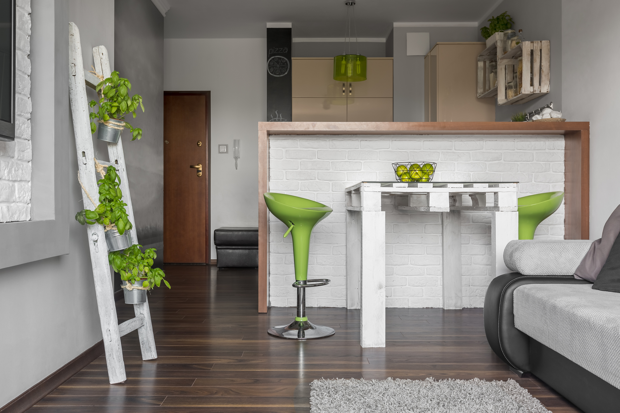 New design flat with open kitchen, blackboard, small dining set, sofa and decorative green details