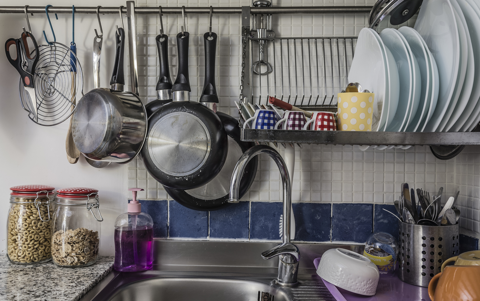 Plates and cups left to dry on a iron dish rack
