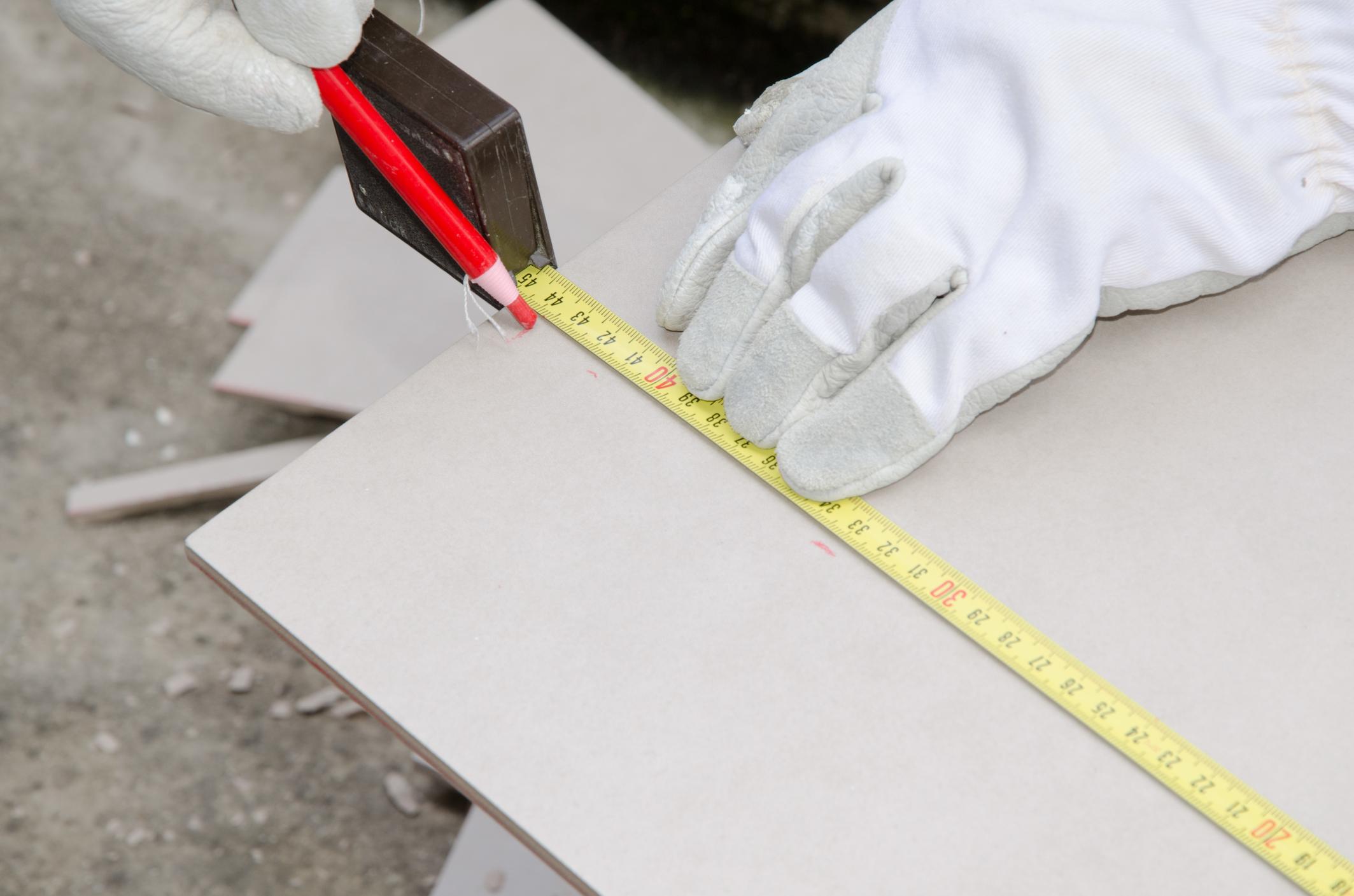Tiler measuring tile before cutting