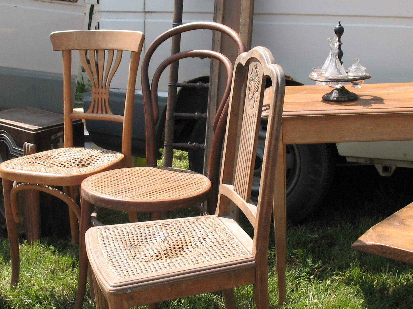 Three antique wooden chairs and table displayed at an outdoor flea-market