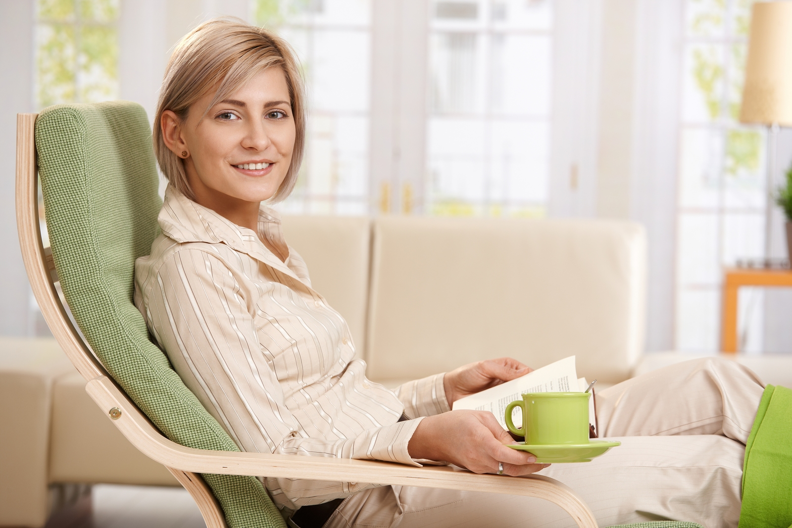 Woman relaxing in armchair at home, reading book , holding coffee cup
