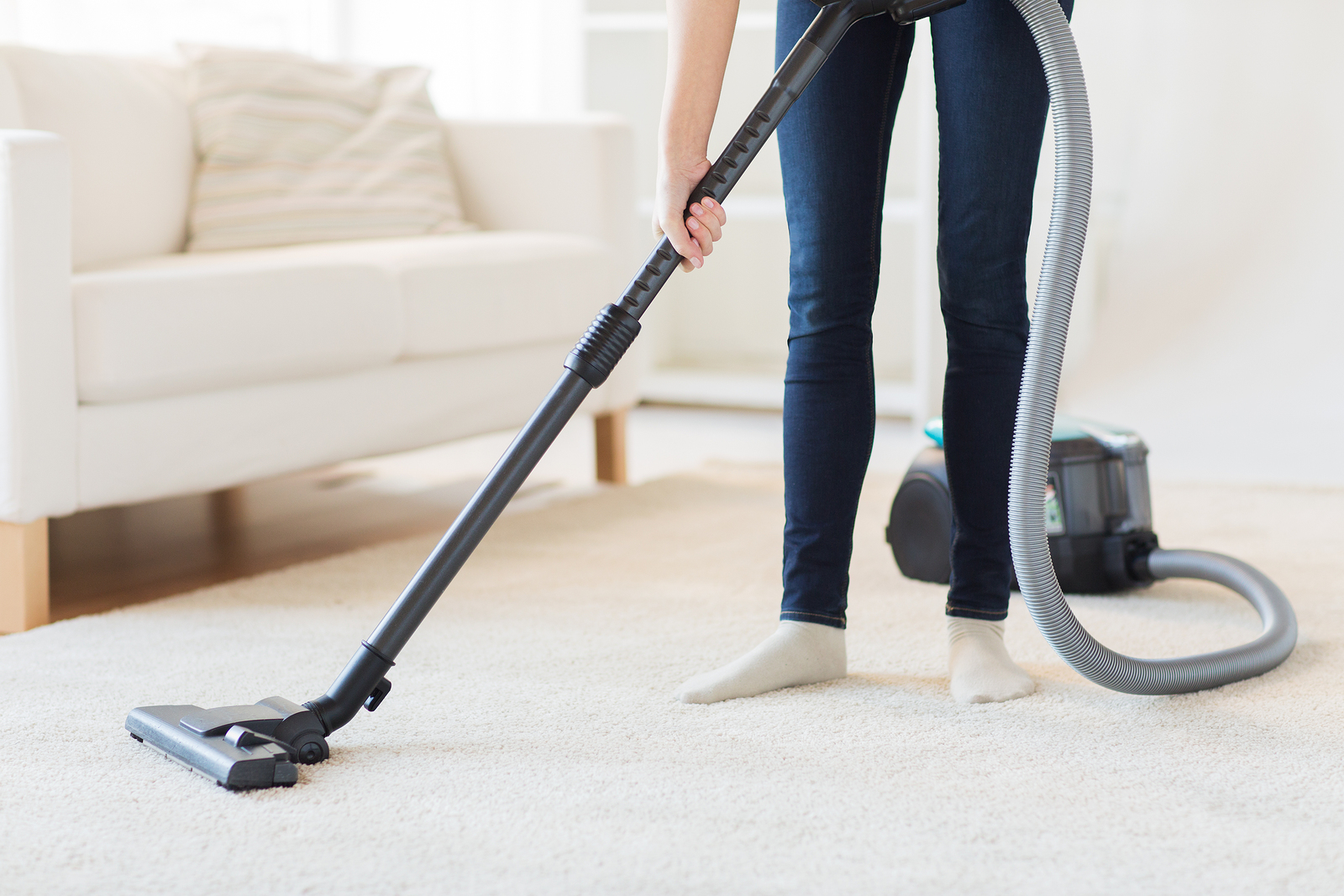 Woman with legs vacuum cleaner cleaning carpet at home