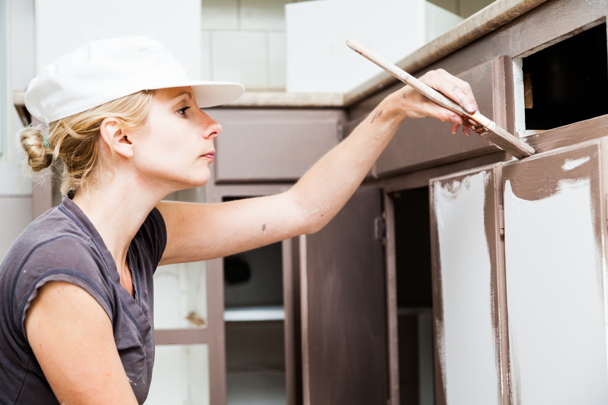 Closeup of Woman Painting Kitchen Cabinets