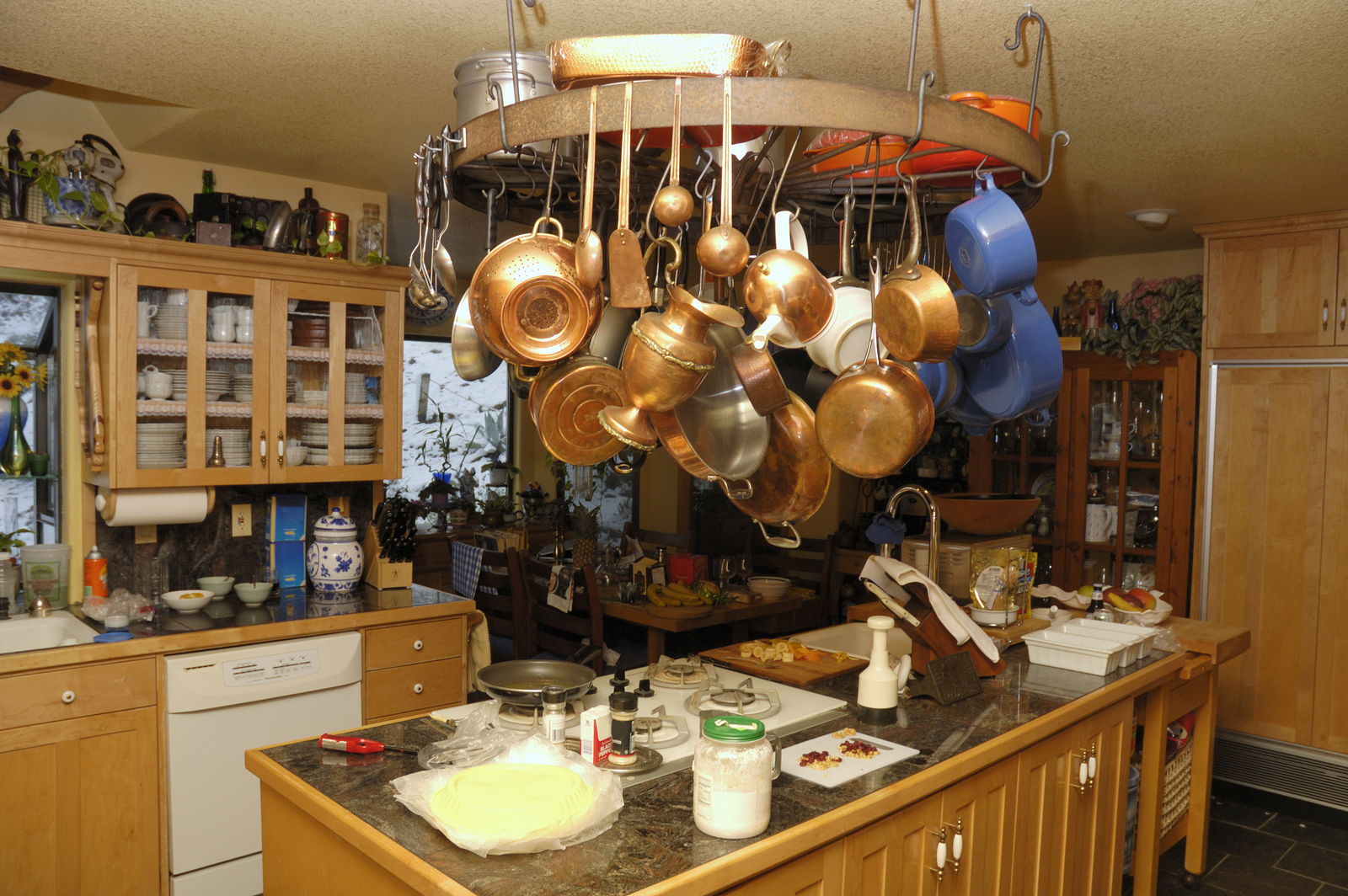 A well used kitchen with pots and pans hanging from wheel over island